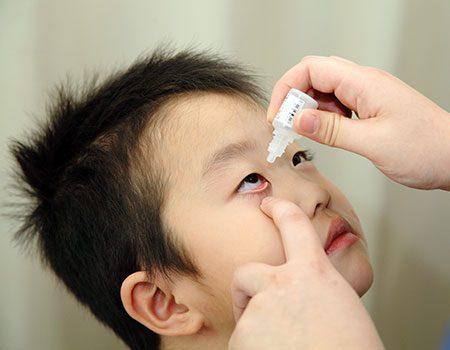子どもに目薬を点眼している写真